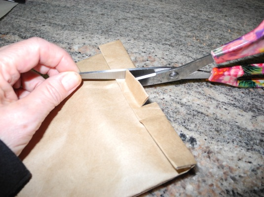 Seal your popcorn bag by cutting into your fold and folding down tightly.